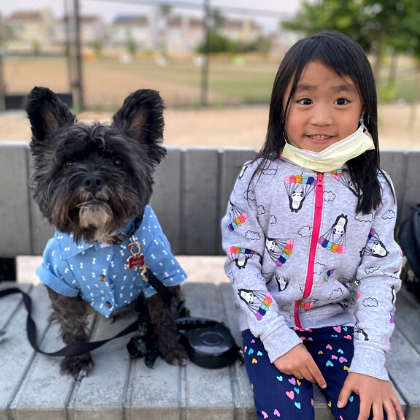 Adorable Dog in a button up shirt sitting next to a young smiling girl wearing a face mask.